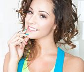 Portrait of happy attractive young brunette woman with colorful nails