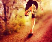 an athletic pair of legs running on a path during sunrise or sunset - healthy lifestyle concept don