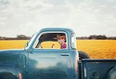 a handsome man with a cowboy hat on driving a truck past a field full of yellow flowers