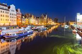 GDANSK, POLAND - 8 AUGUST 2014: Old town of Gdansk at night with reflection in Motlawa river. Gdansk is the historical capital of Polish Pomerania with medieval old town architecture.