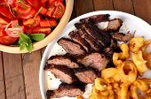 image of flank steak  - Flank steak with fries onion rings and salad - JPG