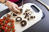 Senior woman's hand chopping mushrooms on cutting board