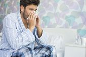 stock photo of blowing  - Sick man blowing his nose in tissue paper on bed at home - JPG