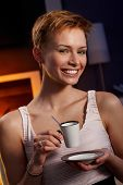 Pretty woman drinking coffee in cosy room, smiling happy.
