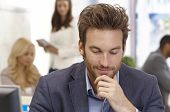 Young businessman thinking in office hand on chin, looking down.