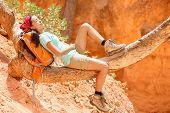 Resting relaxing woman hiker lying down enjoying the sun during hiking travel trek Bryce Canyon National Park landscape, Utah, USA. Beautiful young female hiker.