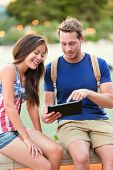 University students on tablet computer. Happy couple using app outside. Asian woman and young Caucas
