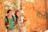 Hiking - young couple of hikers relaxing resting in Bryce Canyon walking smiling happy together. Mul