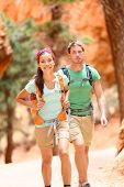 People hiking - couple hikers in Bryce Canyon walking smiling happy together. Multiracial couple, yo