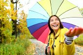 Autumn / fall woman happy in rain with umbrella. Female model looking up at clearing sky joyful on r