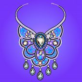 Woman's Necklace Of Precious Stones On A Purple Background