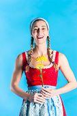 Woman in dirndl dress holding flowers