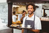 stock photo of waiter  - Handsome waiter smiling at camera holding tray at the coffee shop - JPG