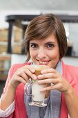 Pretty brunette enjoying her latte at the coffee shop