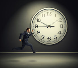 image of running-late  - smiley running businessman and big white clock in dark room - JPG