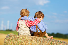 pic of haystacks  - Two little children and friends sitting on hay stack or bale and speaking on yellow wheat field in summer - JPG