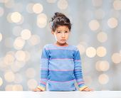 people, childhood and emotions concept - sad little girl over holidays lights background