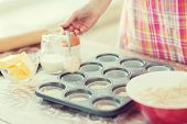 cooking and home concept - close up of hand filling muffins molds with dough