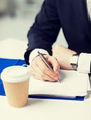 businessman with coffee cup writing something on the paper