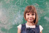 Portrait Of Girl Standing In Fron Off Drawn Chalkboard In Elementary School
