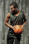 Afro-american muscular man holding basketball