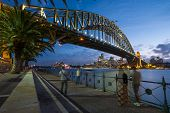 People Taking Pictures Of Sydney Harbour Bridge At Dusk