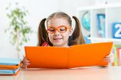 Happy funny child girl in glasses reading a book in primary school