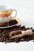 Coffee Grains, Wooden Spoon And White Cup