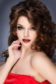 Beautiful brunette with gorgeous curly hair. Fashion shot of a gorgeous young woman in elegant red d