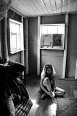 sad looking girl sitting on the floor in small room in black and white