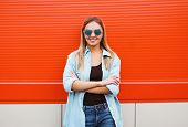 Cool Pretty Woman In Sunglasses Outdoors Posing In Urban Style Against Colorful Wall