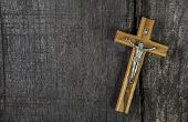 Jesus on cross: decoration on wooden background. Idea for a condolence card.