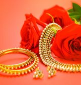 image of bangles  - Traditional indian gold necklace and bangles set with rose flower on red background - JPG
