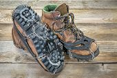 old hiking boots with trail crampons on wood background
