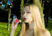 Blonde Woman Blowing Soap Bubbles