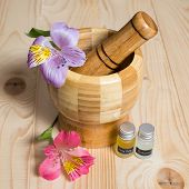 Wooden bamboo pounder with bottles of oils and flowers