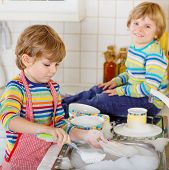 Two Little Blond Twins Boys Washing Dishes In Domestic Kitchen