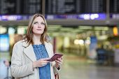 picture of board-walk  - Young woman at international airport checking electronic board and waiting for her flight. Female passenger with european passport at departure terminal indoors.