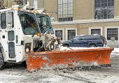 Truck with snowplow clearing street after snowstorm
