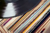 stock photo of lp  - an old dusty collection of vinyls with one LP at the top