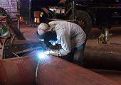 picture of pipe-welding  - welder in factory with protective equipment welding metal pipes - JPG