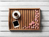 Instant photo frame and many cute hearts with cup of coffee on wood.