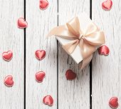 Gift box with small hearts on old white wood table