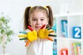 little girl with hands in paint on nursery background