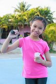 stock photo of shuttlecock  - Cute little girl holding badminton racket and shuttlecock Outdoor - JPG