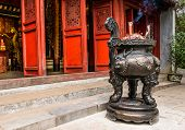 Chinese Joss Stick Pot In Front Of Red Door Of Chinese Temple In Hanoi, Vietnam