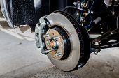 pic of calipers  - Front disc brake on car in process of new tire replacement - JPG