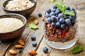stock photo of quinoa  - oatmeal nuts quinoa granola with blueberries on a dark wood background - JPG