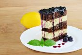 foto of sponge-cake  - Sponge cake with lemon icing and blueberry sauce over wooden table - JPG