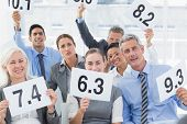 picture of interview  - Smiling interview panel holding score cards in bright office - JPG